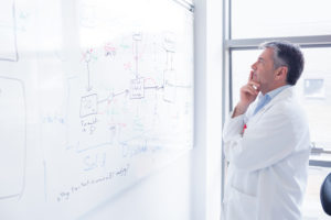 scientist in labcoat looking puzzled at whiteboard