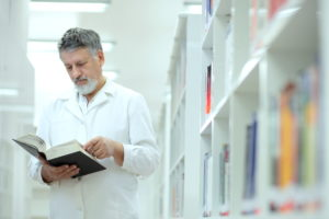 male scientist in white lab coat in library reading book