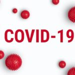 The words COVID-19 surrounded by virus-like particles.
