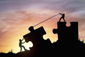 Silhouette of two people pulling giant-size jigsaw puzzle pieces together with chains, to visualise the concept of people working together to end the reign of the journal impact factor