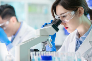 close up of asian female scientist use microscope in the laboratory