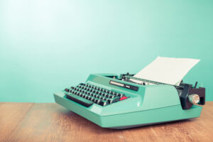 Retro old typewriter with paper on wooden table front mint green background, such as could be used to write an introduction