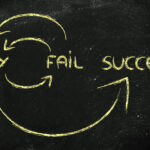 "Blackboard showing the words ""try"", ""fail"" and ""success"", linked by arrows"